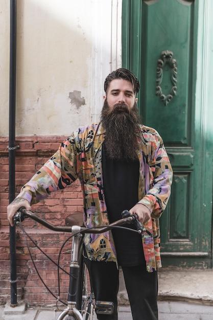 Porträt eines bartmannes mit seinem fahrrad, das kamera betrachtet Kostenlose Fotos