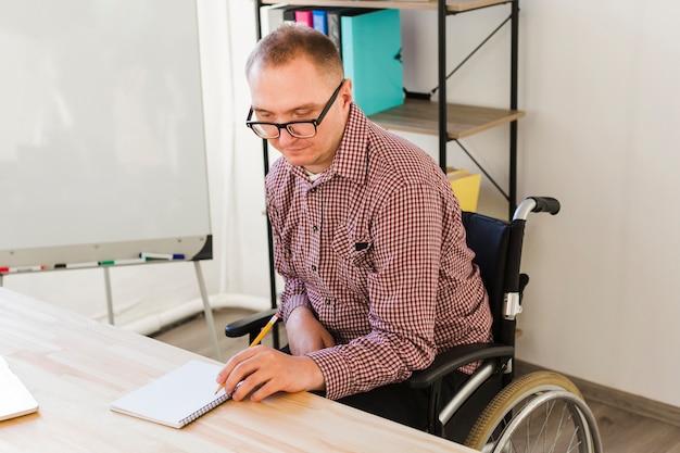 Porträt eines behinderten mannes, der am projekt arbeitet Kostenlose Fotos