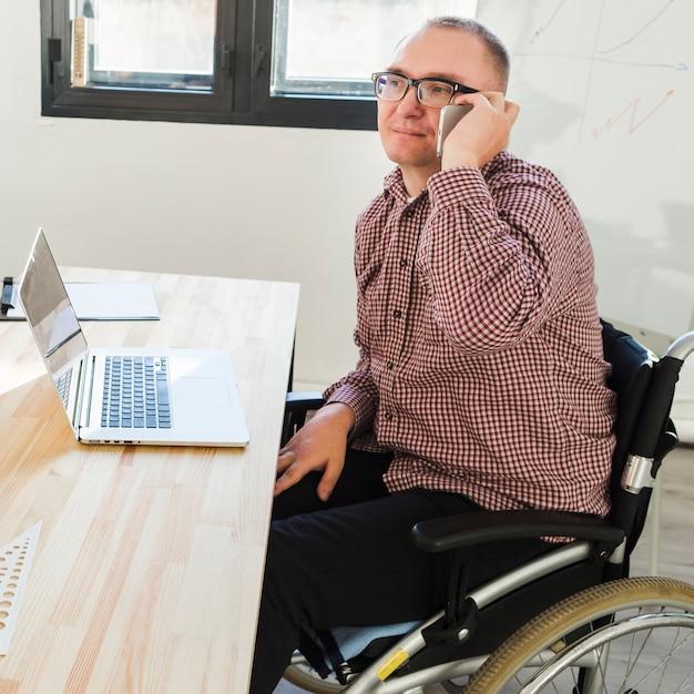 Porträt eines behinderten mannes, der im büro arbeitet Kostenlose Fotos