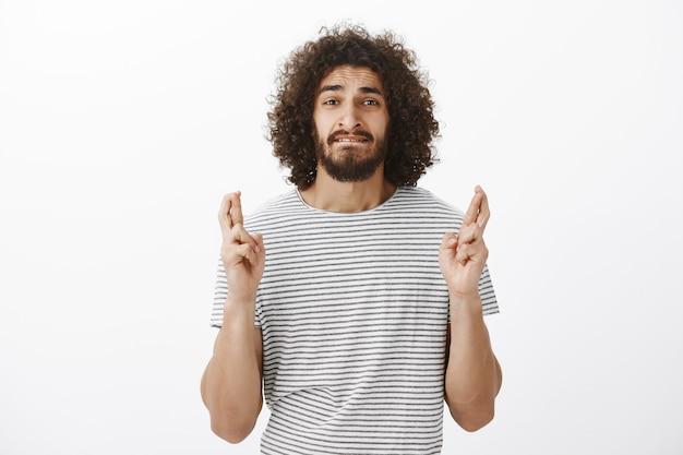 Porträt eines besorgten gutaussehenden hispanischen mannes mit afro-frisur in gestreiftem t-shirt, ängstlicher lippe beißen und daumen drücken in der hoffnung oder im beten, wunschtraum wird wahr Kostenlose Fotos