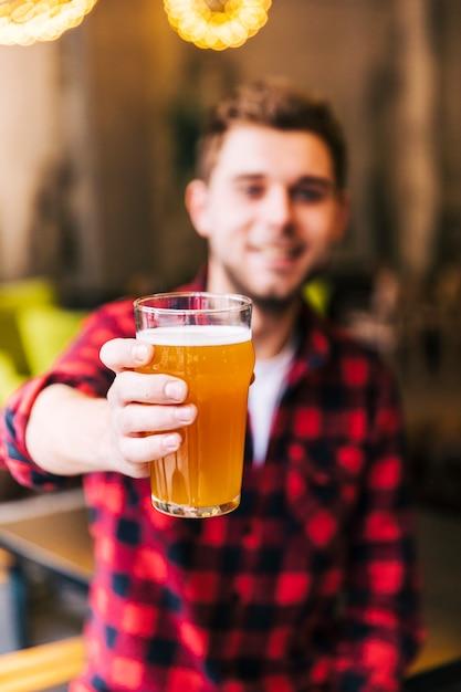 Porträt eines defokussierten jungen mannes, der glas bier hält Kostenlose Fotos