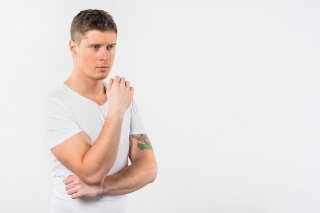 Porträt eines durchdachten jungen mannes, der gegen weißen hintergrund steht Kostenlose Fotos