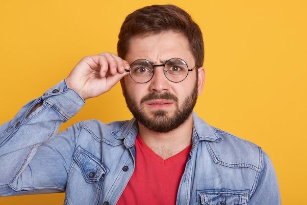 Porträt eines ernsten mannes mit dunklem haar und bart, der seine brille berührt, mann, der stilvolle jeansjacke trägt und gegen gelbe wand aufwirft Kostenlose Fotos