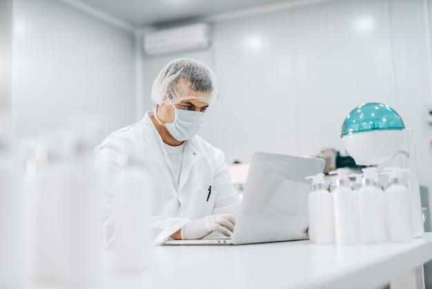Porträt eines ernsthaften chemikers mit maske, gummihandschuhen, haarnetz und steriler uniform, die am laptop im labor arbeiten Premium Fotos