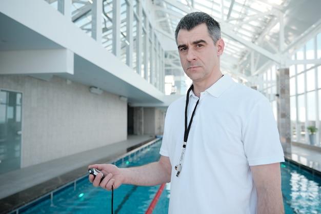 Porträt eines ernsthaften strengen reifen trainers mit pfeife unter verwendung der stoppuhr, während zeitschwimmer beim training Premium Fotos