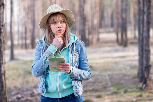 Porträt eines erwogenen weiblichen wanderers, der die karte in der hand weg schaut hält Kostenlose Fotos