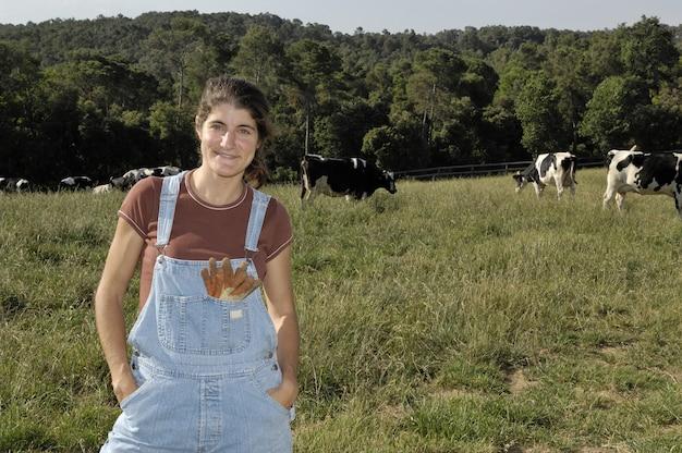 Porträt eines frauenlandwirts mit einigen kühen Premium Fotos