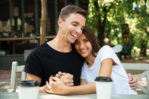 Porträt eines fröhlichen attraktiven paares, das kaffee trinkt Kostenlose Fotos