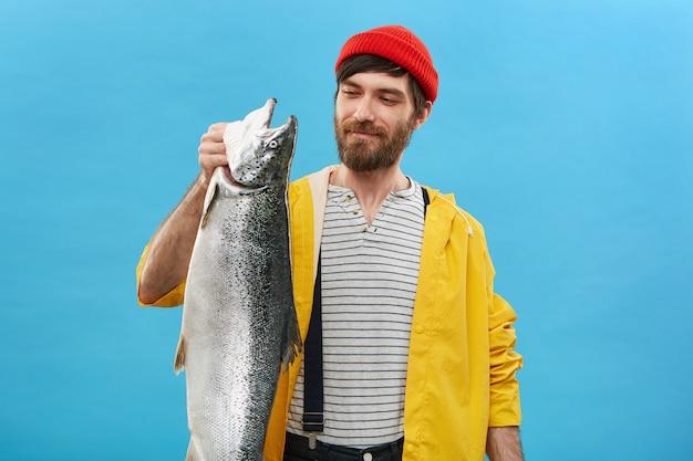 Porträt eines fröhlichen fischers, der einen roten hut, eine gelbe jacke und einen overall trägt und mit erfreutem ausdruck auf seinen fang schaut, der stolz ist. Kostenlose Fotos