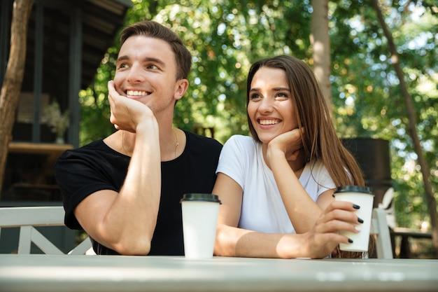 Porträt eines fröhlichen jungen paares, das kaffee trinkt Kostenlose Fotos