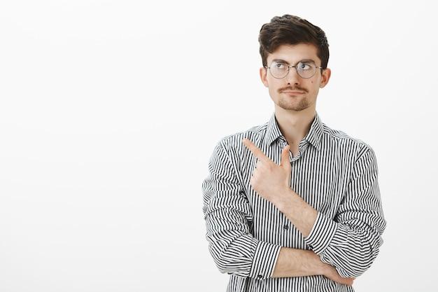Porträt eines gleichgültigen, nicht überraschten, nerdigen mannes mit schnurrbart, der mit einem engen lächeln auf die obere linke ecke zeigt und schaut, unzufrieden mit dem thema ist und über einer grauen wand steht Kostenlose Fotos