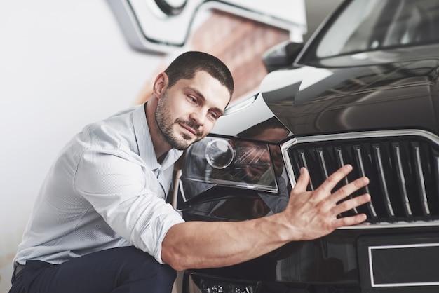 Porträt eines glücklich lächelnden mannes, der ein neues auto in der kabine wählt. Kostenlose Fotos