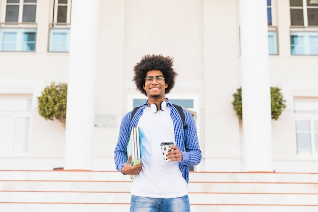 Porträt eines glücklichen afrikanischen jugendlichen männlichen studenten, der die bücher und mitnehmerkaffeetasse stehen vor college hält Kostenlose Fotos