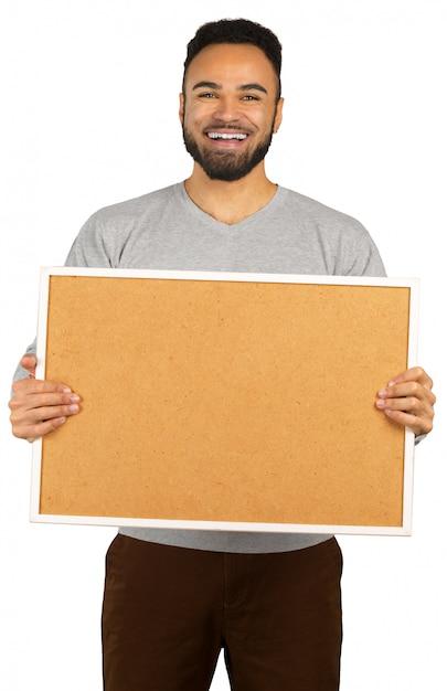 Porträt eines glücklichen afroamerikanischen mannes, der leeres brett lokalisiert auf einem weiß hält Premium Fotos