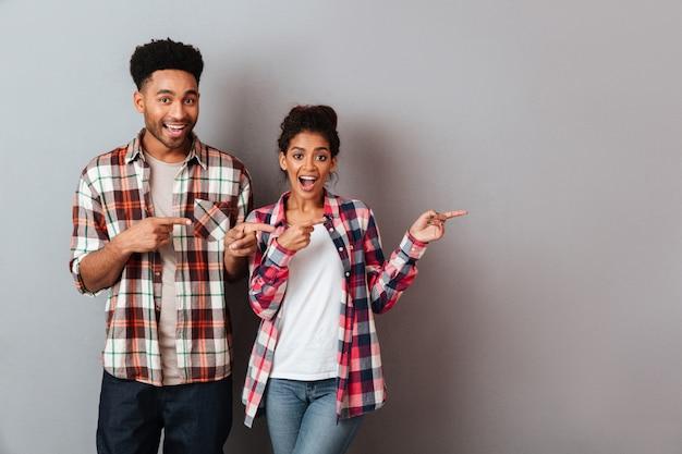 Porträt eines glücklichen jungen afrikanischen paares, das zusammen steht, zeigend seite mit den fingern Kostenlose Fotos