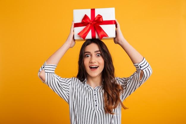 Porträt eines glücklichen jungen mädchens, das geschenkbox hält Kostenlose Fotos