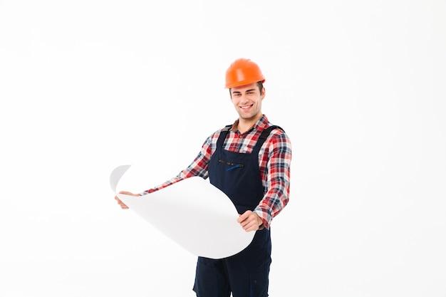 Porträt eines glücklichen jungen männlichen erbauers, der papierentwurf hält Kostenlose Fotos