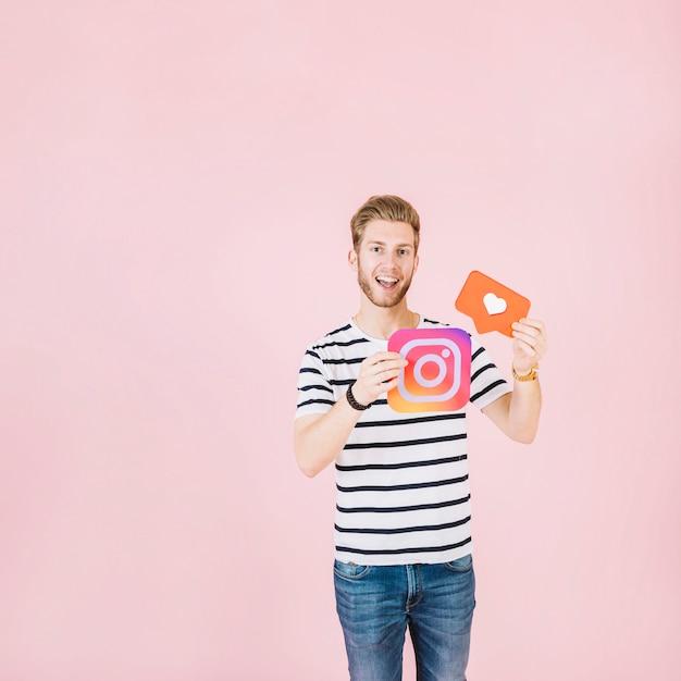 Porträt eines glücklichen jungen mannes, der instagram hält und mögen ikone Kostenlose Fotos