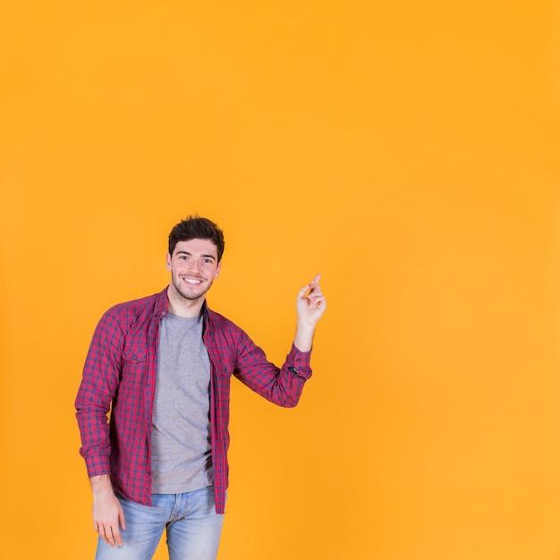 Porträt eines glücklichen jungen mannes, der seinen finger gegen einen orange hintergrund zeigt Kostenlose Fotos