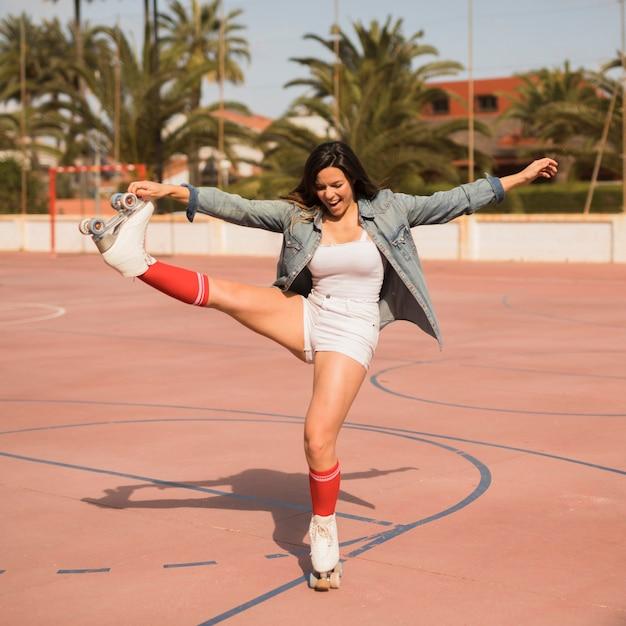 Porträt eines glücklichen jungen weiblichen schlittschuhläufers, der auf einem bein steht Kostenlose Fotos