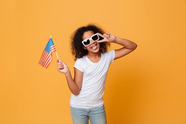 Porträt eines glücklichen kleinen afrikanischen mädchens in der sonnenbrille mit amerikanischer flagge Kostenlose Fotos