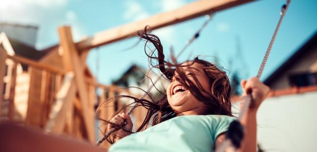 Porträt eines glücklichen kleinen mädchens, das auf einem schwingen und einem lächeln sitzt Premium Fotos