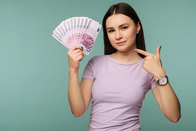 Porträt eines glücklichen mädchens, das finger auf bündel geldbanknoten zeigt, die über blau lokalisiert werden Premium Fotos