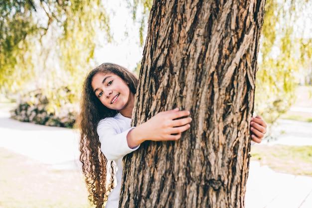 Porträt eines glücklichen mädchens, das großen stamm im garten umarmt Kostenlose Fotos