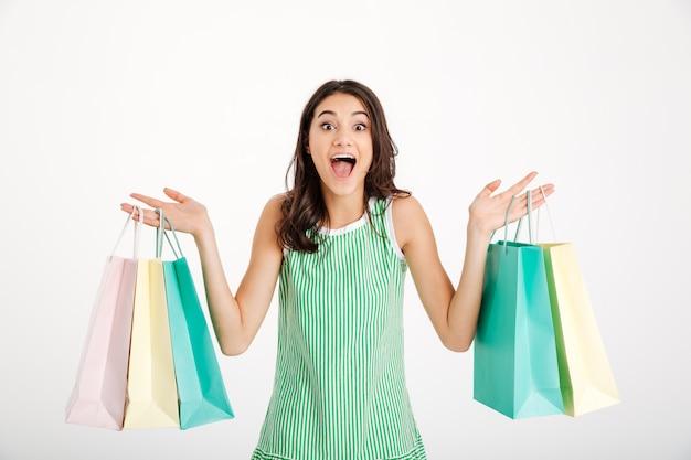 Porträt eines glücklichen mädchens im kleid, das einkaufstaschen hält Kostenlose Fotos