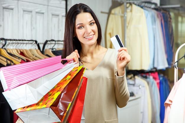Porträt eines glücklichen mädchens mit einkaufstaschen und kreditkarte in einem bekleidungsgeschäft. Premium Fotos