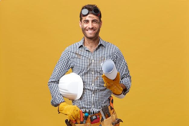 Porträt eines glücklichen männlichen arbeiters in freizeitkleidung, schutzbrillen, handschuhe und werkzeuggürtel an der taille mit blaupause und helm mit angenehmem lächeln, das sich über seinen erfolg bei der arbeit freut Kostenlose Fotos