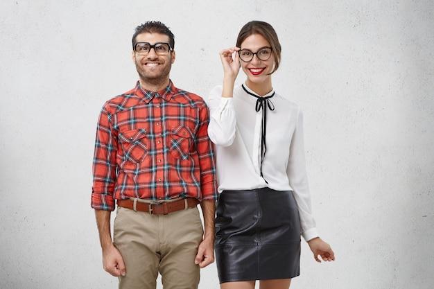 Porträt eines glücklichen männlichen nerds und seiner freundin, die froh sind, freizeit zusammen zu verbringen Kostenlose Fotos