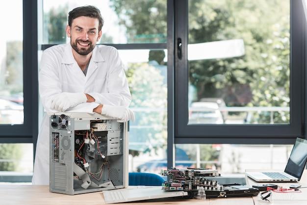 Porträt eines glücklichen männlichen technikers mit defektem computer Kostenlose Fotos