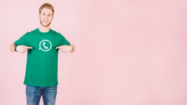 Porträt eines glücklichen mannes, der auf sein t-shirt mit whatsapp ikone zeigt Kostenlose Fotos