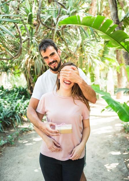 Porträt eines glücklichen mannes, der überraschung mit geschenk für seine freundin im wald macht Kostenlose Fotos