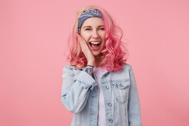 Porträt eines glücklichen süßen mädchens mit rosa haaren und tätowierter hand, geschmeichelt durch das kompliment, lacht und berührt die stehende wange, trägt ein weißes t-shirt und eine jeansjacke. Kostenlose Fotos