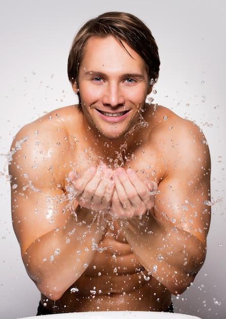 Porträt eines gutaussehenden lächelnden mannes, der sein gesundes gesicht mit wasser auf grauer wand wäscht. Kostenlose Fotos