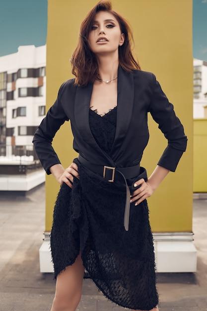 Porträt eines herrlichen hellen kleides der brunettefrau in mode, das auf dem dach eines gebäudes aufwirft Premium Fotos