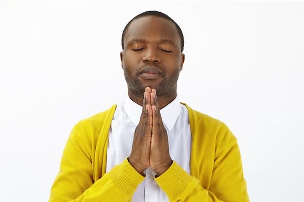 Porträt eines hoffnungsvollen erwachsenen afroamerikaners, der die augen schließt und die handflächen zusammenpresst, betet und auf das beste hofft. ruhiger friedlicher dunkelhäutiger mann, der hände in namaste hält, während er meditiert Kostenlose Fotos