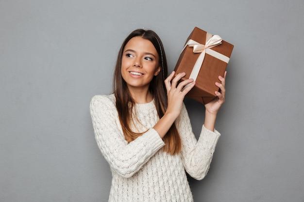 Porträt eines hübschen jungen mädchens im pullover, der geschenk hält Kostenlose Fotos