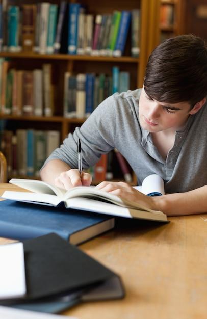 Porträt eines hübschen studenten, der einen aufsatz schreibt Premium Fotos