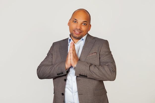 Porträt eines jungen afroamerikanischen geschäftsmannes, der lächelt, handflächen vor sich zusammenhält, seine hände in einer gebetsgeste hält und um vergebung für einen fehler bittet. Premium Fotos