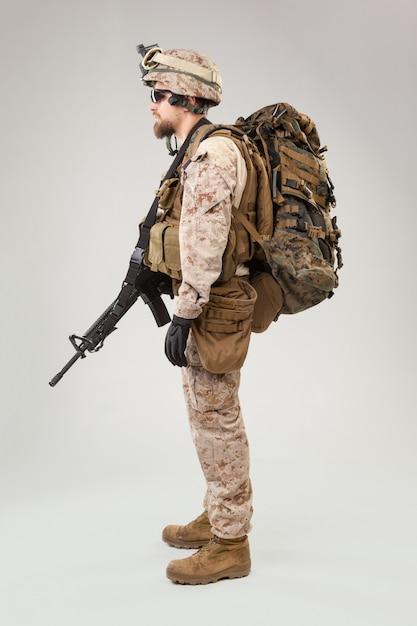 Porträt eines jungen amerikanischen us marine corps-soldaten über grau Premium Fotos