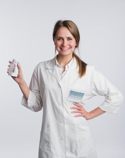 Porträt eines jungen apothekers, der pillen zeigt Premium Fotos