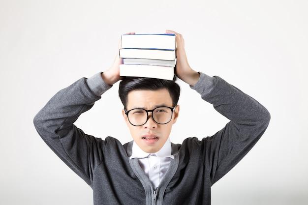 Porträt eines jungen asiatischen studenten, der bücher auf seinem kopf hält. atelieraufnahme auf weißem hintergrund. konzept für bildung Premium Fotos