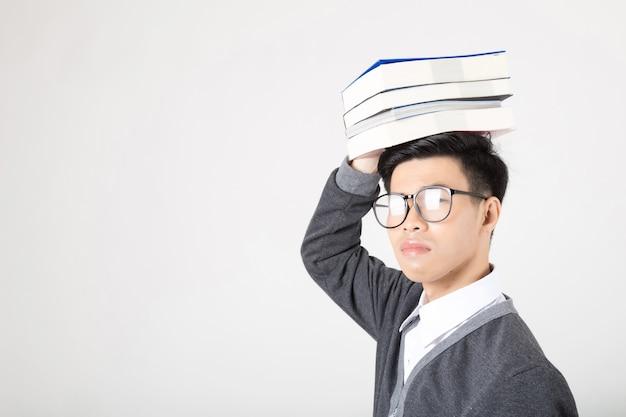 Porträt eines jungen asiatischen studenten, der bücher auf seinem kopf hält. Premium Fotos