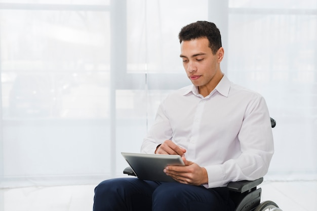 Porträt eines jungen geschäftsmannes, der auf dem rollstuhl betrachtet digitale tablette sitzt Kostenlose Fotos