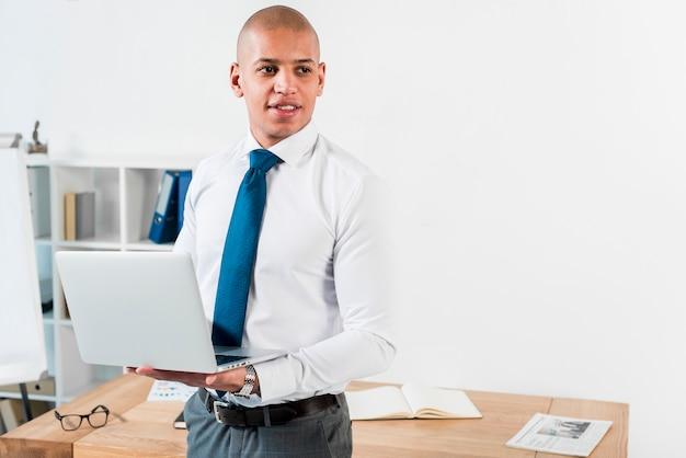 Porträt eines jungen geschäftsmannes, der in der hand einen offenen laptop weg schaut hält Kostenlose Fotos