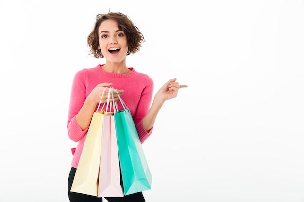 Porträt eines jungen glücklichen mädchens, das einkaufstaschen hält Kostenlose Fotos
