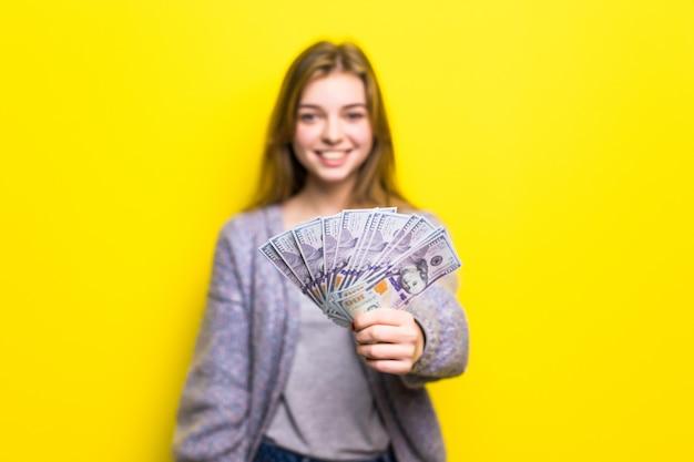 Porträt eines jungen lässigen jugendlich mädchens, das geldbanknoten isoliert hält Kostenlose Fotos
